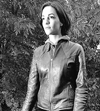 a woman in a leather jacket walks through a path